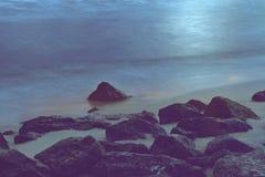 Kamienie na plaży z spokojną wodą morską Zdjęcia Royalty Free