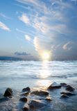 Kamienie na seawater z zmierzchem i chmurami Fotografia Royalty Free