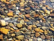 Kamienie różni kolory pod wodą Zdjęcia Royalty Free