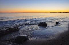 Kamienie w wodzie, fala na piaskowatej plaży zatoka Finlandia na cudownym zmierzchu Fotografia Royalty Free