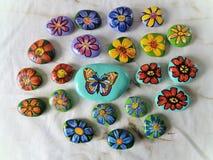 Kamienie z malującymi kwiatami i motylem Obrazy Stock