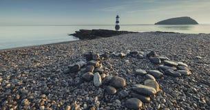 Kamienista plaża Penmon przy wschodem słońca fotografia stock