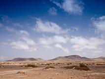Kamienista pustynia i odległe góry Fotografia Stock