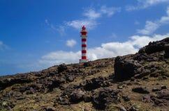 Kamienisty krajobraz z latarnią morską i niebieskim niebem z białą i czerwoną zdjęcia stock