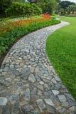 Kamienna blokowa spacer ścieżka w parku z zieloną trawą i flowe Obrazy Royalty Free