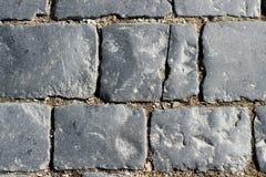 Kamienna bruk tekstura, granitowy cobblestoned bruku tło, brukujący kamienni drogowi miarowi kształty, abstrakcjonistyczny tło fotografia royalty free