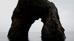 Kamienna grota w morzu przeciw chmurnemu niebu zdjęcie wideo