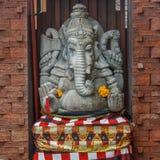 Kamienna Hinduska Ganesha statua w sarongach, dekorujących z nagietkiem kwitnie bali Indonesia obraz stock