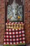 Kamienna Hinduska Ganesha statua w sarongach, dekorujących z nagietkiem kwitnie bali Indonesia obraz royalty free