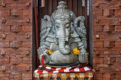 Kamienna Hinduska Ganesha statua w sarongach, dekorujących z nagietkiem kwitnie bali Indonesia zdjęcie stock