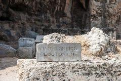Kamienna inskrypcja Ploutonio przed sanktuarium Pluton hades, bóg świat przestępczy w Elefsina Grecja Obrazy Stock