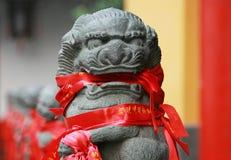 Kamienna lew postać z tradycyjnymi modlitewnymi faborkami, Chiny Fotografia Stock