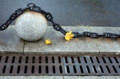 Kamienna piłka z dużym metall łańcuchem, dwa kolorów żółtych jesieni klonu leav obrazy royalty free