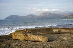 Kamienna plaża, morze, fala i góry daleko od w południe wyspa Mallorca, obrazy stock
