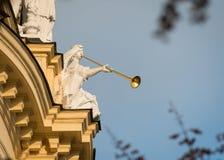 Kamienna postać z złotej trąbki obsiadaniem na starym budynku zdjęcia stock