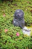 Kamienna statua Jizo na ziemi zakrywającej zieleni gwiazdy czerwieni i mech liśćmi klonowymi podczas jesieni w ogródzie przy Enko Obrazy Stock