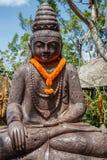 Kamienna statua Siedzieć Buddha pod drzewem, Bali, Indonezja Pionowo wizerunek zdjęcie royalty free