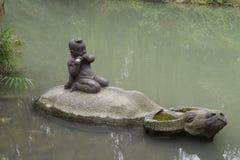 Kamienna statua w stawie w Huanhuaxi parku, Chengdu, Chiny fotografia stock