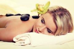 Kamienny masaż, kobieta dostaje gorącego kamiennego masaż przy zdroju salonem Zdjęcie Stock