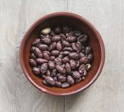 Kamienny puchar z czekoladowymi arachidami na drewnianym tle obrazy stock