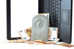 kamienny zabytek, nagrobek z bitcoin symbolem na stosie banknoty przed notatnikiem/ fotografia royalty free