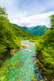 Kamikochi Azusa River Mount Hotaka Dake View. The crystal clear water of the Azusa river winds thru pristine forest with  landscape view of Mount Hotaka-Dake in Royalty Free Stock Photography