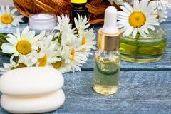 Kamilleetherische olie in een glaskruik naast kamilles en kosmetische zeep stock foto