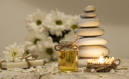 Kamillenätherisches öl, Blumenstrauß von Kamillenblumen, Stapel Felsen und Kerze stockbilder
