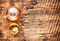 Kamillenkräutertee in einer Teekanne und eine Schale und eine Kamille blüht Stockfoto