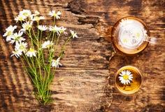Kamillenkräutertee in einer Teekanne und eine Schale und eine Kamille blüht Stockbild