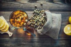 Kamillenteeschale, Tasche des groben Sackzeugs von trockenen Gänseblümchenblumen, Honigglas und Zitronenscheiben Lizenzfreies Stockbild