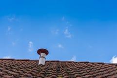 Kamin auf einem Kabinendach mit Himmel Stockfotografie