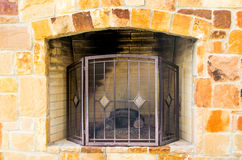 Kamin des bunten Kalksteins im Freien mit schwarzem Gitter Lizenzfreies Stockfoto