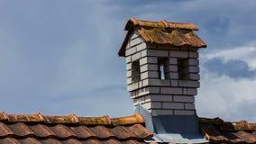 Kamin mögen ein kleines Haus auf dem Dach vor grauen Wolken stock video