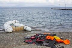 Kamizelki Ratunkowe odrzucać na plaży Uchodźcy przychodzący od Turcja w nadmuchiwanej łodzi Fotografia Royalty Free