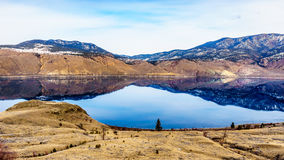 Kamloops Lake with the surrounding mountains reflecting on the quiet surface Royalty Free Stock Photos