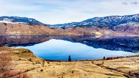 Kamloops sjö med de omgeende bergen som reflekterar på den tysta yttersidan Arkivfoto