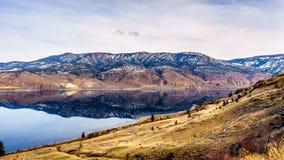 Kamloops sjö med de omgeende bergen som reflekterar på den tysta yttersidan Fotografering för Bildbyråer