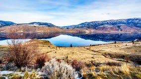 Kamloopsmeer met de omringende bergen die de stille oppervlakte overdenken Royalty-vrije Stock Foto's