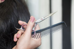 Kamm und Scheren in der Hand von Friseuren Lizenzfreie Stockfotografie