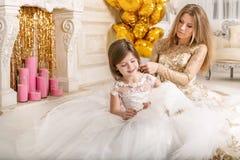 kamma dottermodern Sitta på golvet i en härlig whi Royaltyfria Bilder