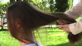 Kamma krullningen av blont hår på flicka`en s head arkivfilmer