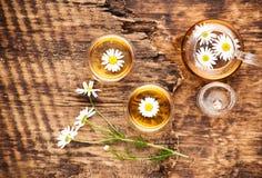 Kamomillörtte i en tekanna och en kopp och en kamomill blommar arkivbilder
