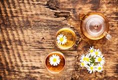 Kamomillörtte i en tekanna och en kopp och en kamomill blommar på en trätabell arkivbild