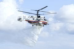 Kamov Ka-32A11BC helicopter dropping water. Russian Ministry for Emergency Situations Kamov Ka-32A11BC firefighting and rescue helicopter flying in the sky royalty free stock photography