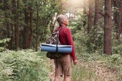 Kamp, avontuur, het reizen, actief recreatieconcept Elderymens met rugzak en deken die in bos wandelen, die onder bomen zich binn stock foto's