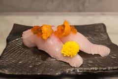 Kampachi sushi med Uni och Ikura överst på den svarta keramiska plattan Royaltyfri Foto
