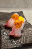 Kampachi sushi with Uni and Ikura on top on black ceramic plate Royalty Free Stock Photo