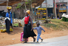 KAMPALA, UGANDA. AUG 26, 2010: Local woman with her son shown in slum of Kampala. Nearly 40% of slum dwellers have a monthly income of just 2,500 shillings stock photo