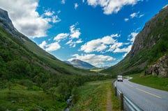 Kampeerauto's en auto's op toneelweg tussen bergen stock foto's